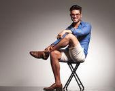 Fotografie lässiger junger Modemann sitzt mit gekreuzten Beinen