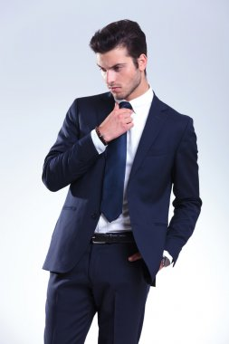 young elegant business man fixing his tie