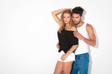 Fashion couple leaning on a white wall