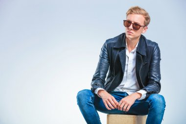 skinny man wearing sun glasses and leather jacket while sitting