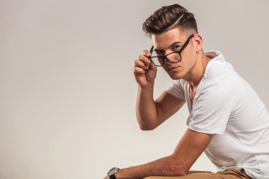 portrait of stylish young man taking off glasses