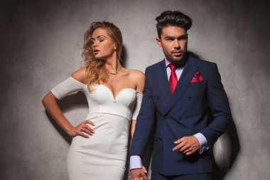 hot elegant couple holding hands and posing in studio