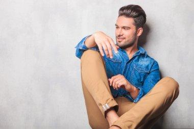 model sitting in studio legs crossed looking way