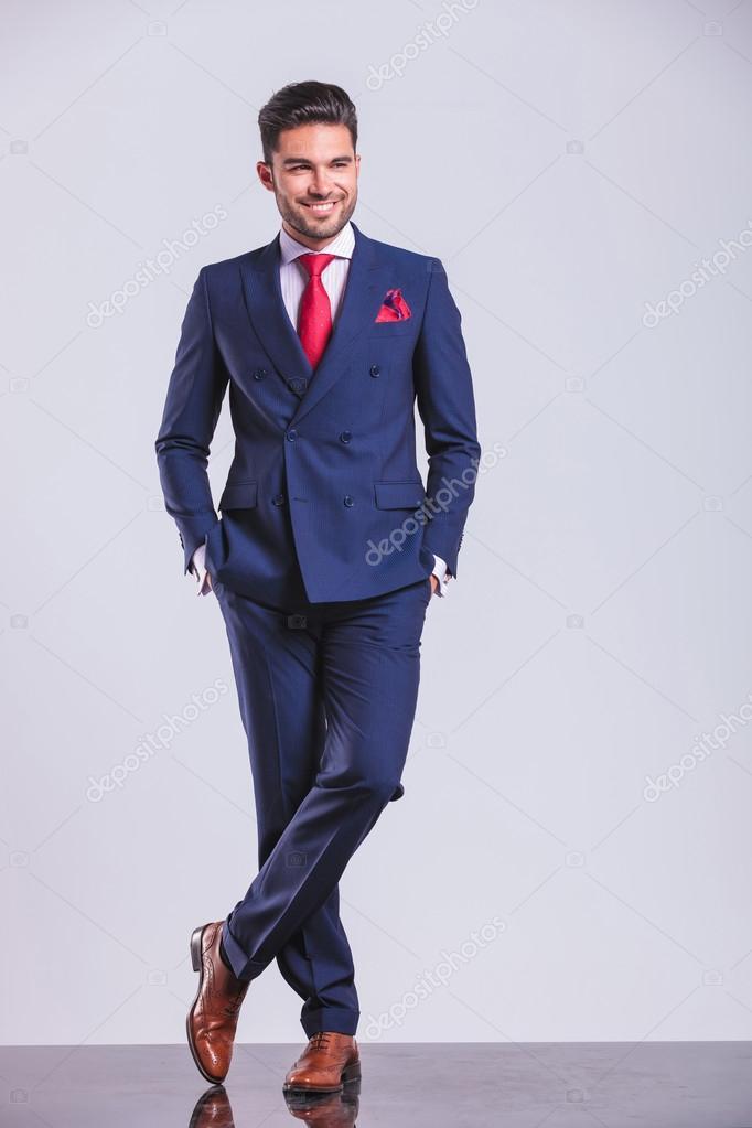 Homme En Costume homme en costume posant jambes croisées tout en ayant les mains dans