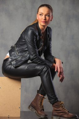 blonde rocker in leather posing smiling seated