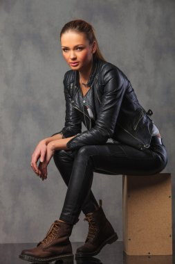 girl in leather jacket posing in studio seated resting