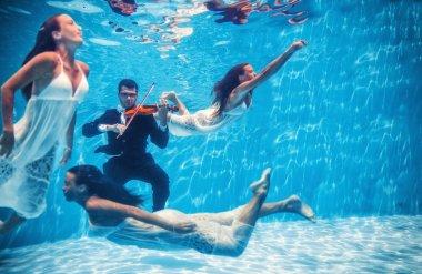 Violinist playing underwater with muse swimming around