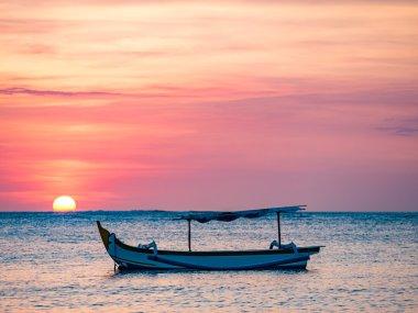 traditional Balinese ships Jukung close on Sanur beach at sunris
