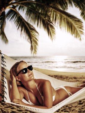 Young beautiful woman relaxing in the hammock