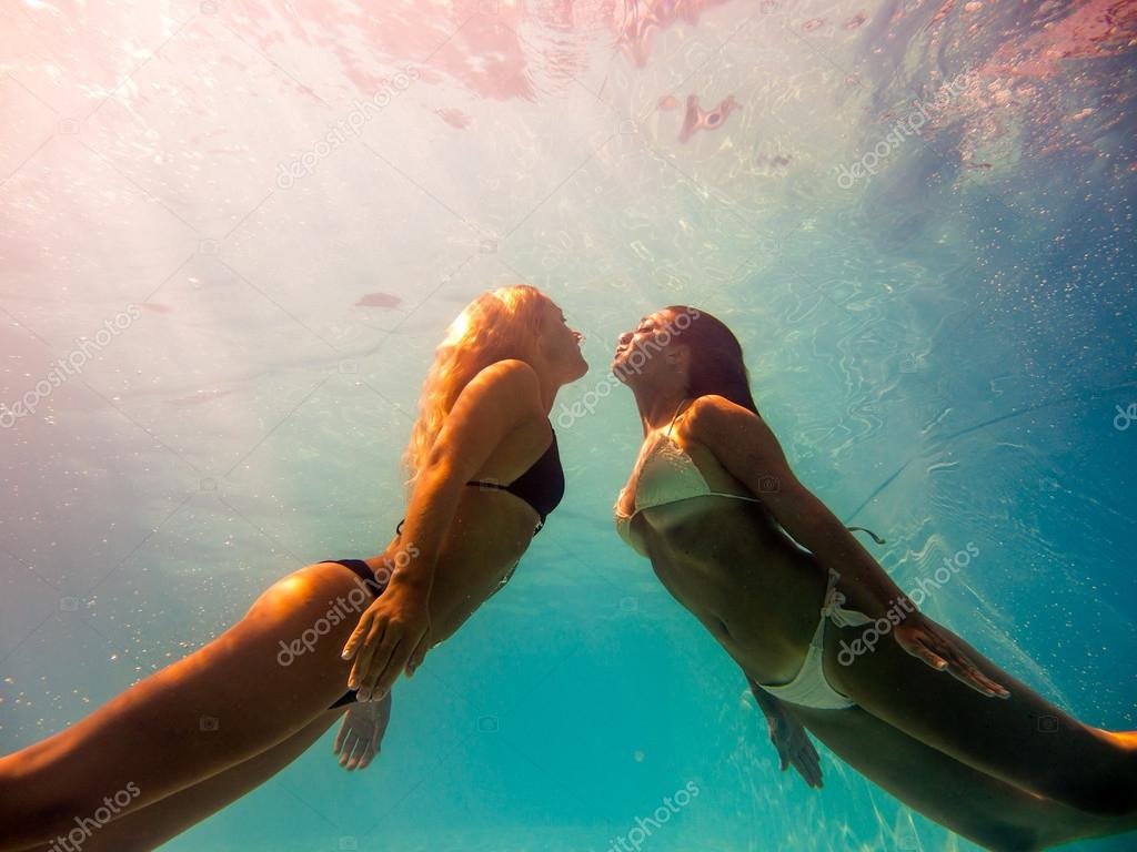 Two young women swimming underwater