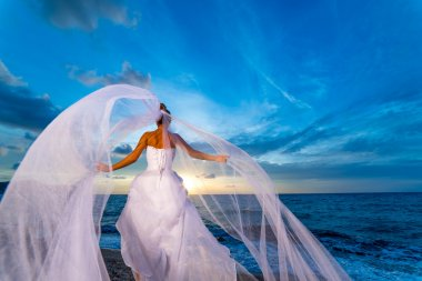 YOung bride by the sea at sunset