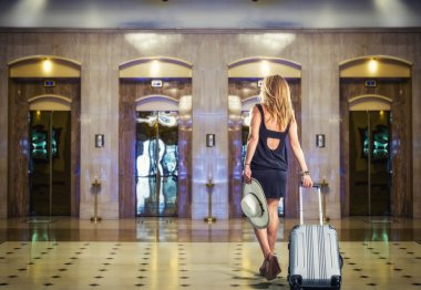 Young Woman with suitcase walking at the hotel