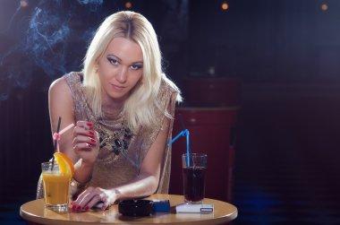 Beautiful elegant lady sitting alone in the night club