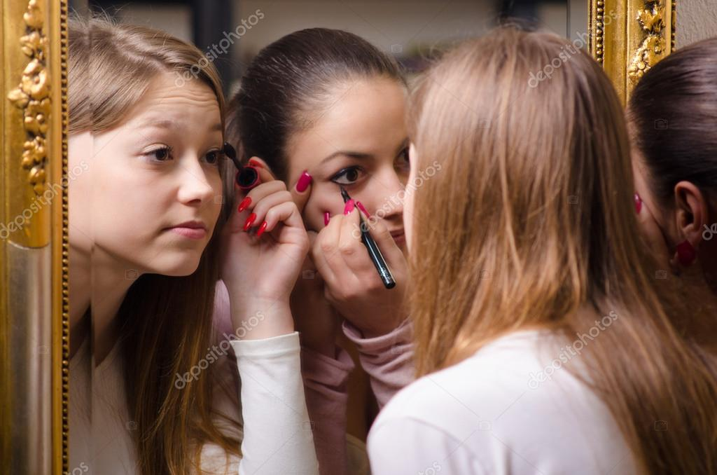 Beautiful teenage girlfriends having fun while putting make up i