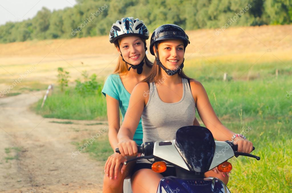 Two teenage girls riding motorcycle in the nature