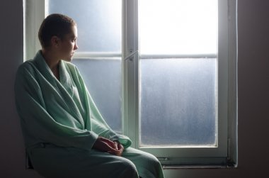Young cancer patient sitting in front of hospital window