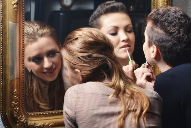 Beautiful girls having fun while putting make up in front of the