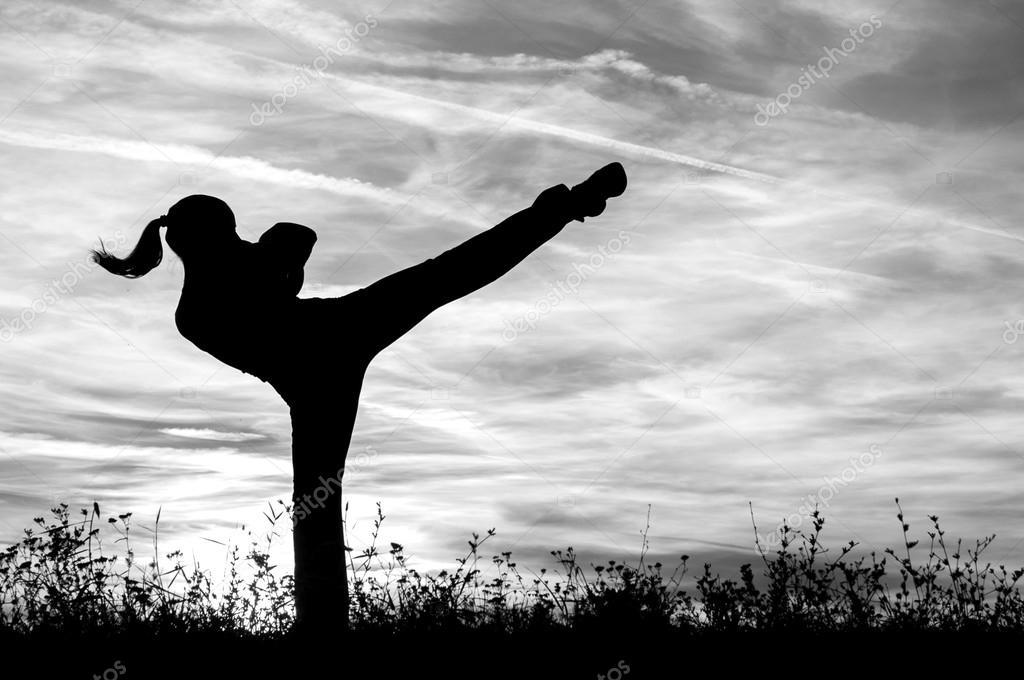 Beautiful kickboxing girl exercising outdoor at sunset