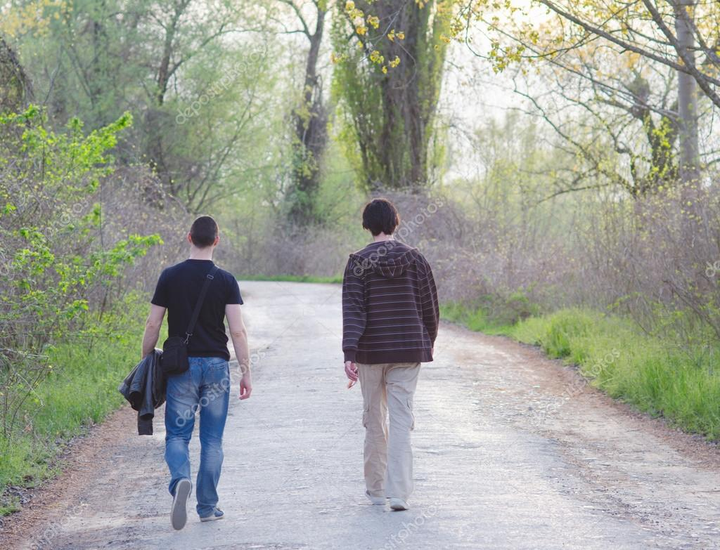 Two male adult friends walking in the nature on sunny spring day