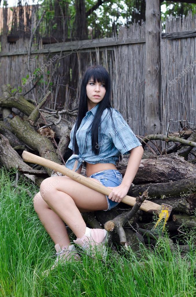 Beautiful sexy female woodcutter resting after cutting wood in s
