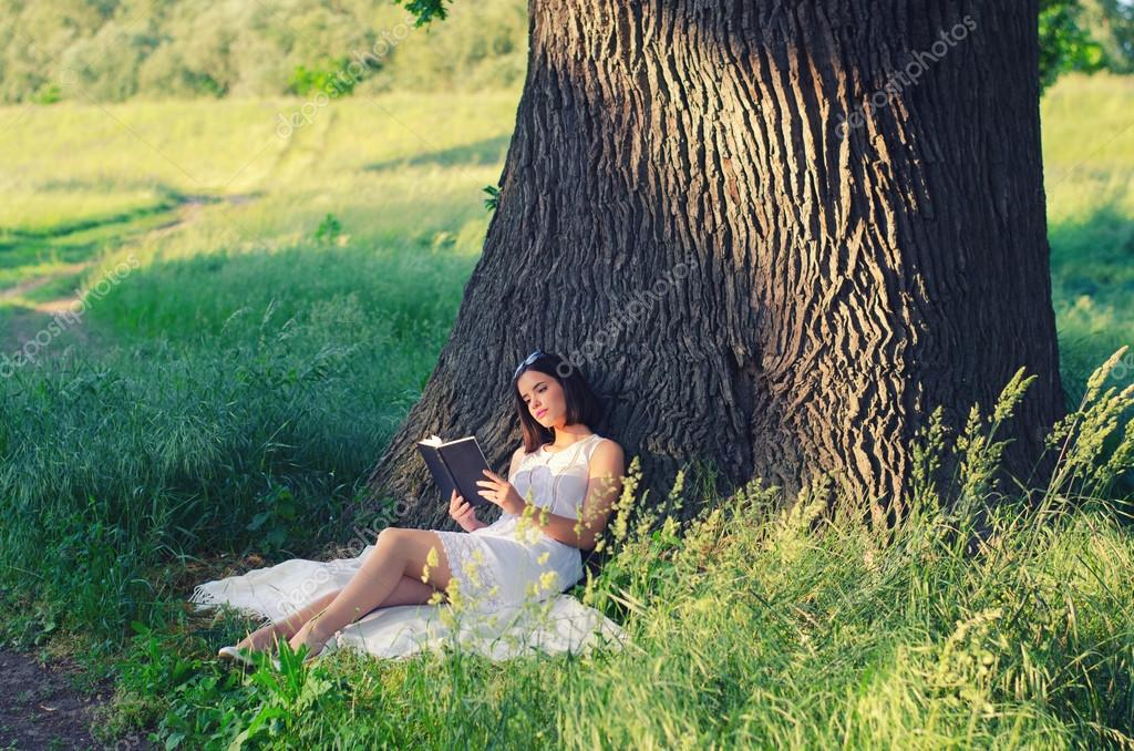 Beautiful young girl sitting on blanket under giant oak and reading book in summer