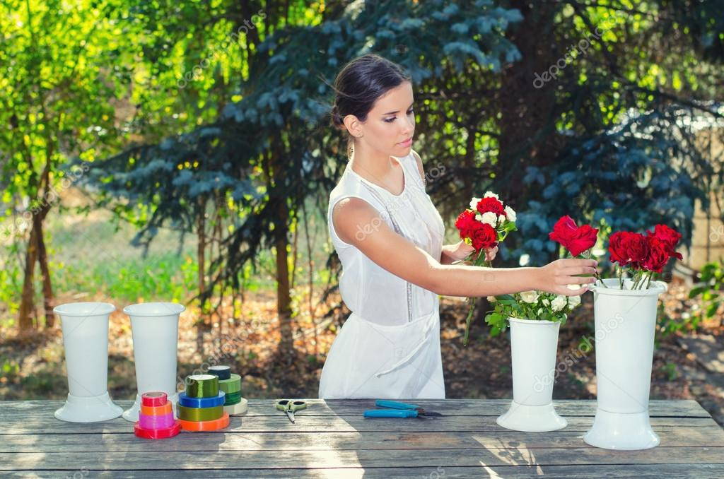 Beautiful girl in white dress making bouquets of roses on sunny summer day