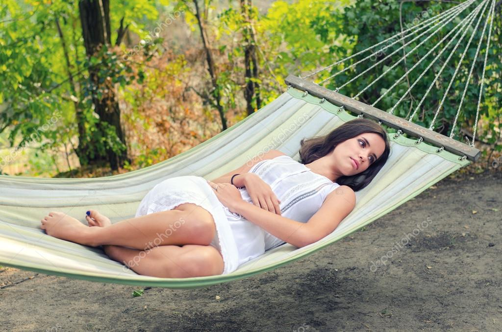 Beatiful sad girl in white dress lying in hammock in summer forest