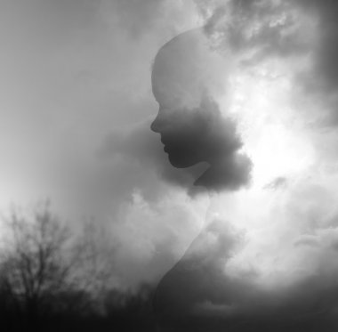 Double exposure image made of silhouette of young girl emerging from  clouds
