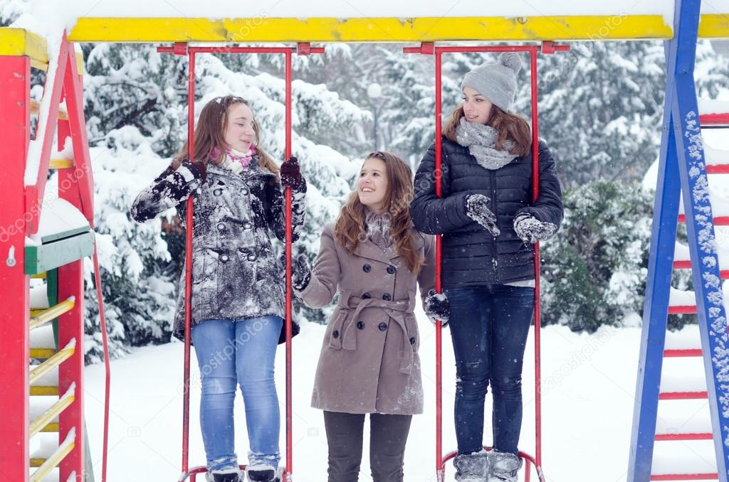 Teenage girls having fun in the snow on beautiful winter day