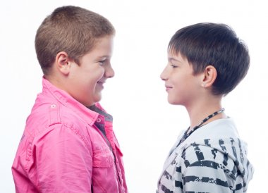 Two teenage boys smiling at each other isolated on white background