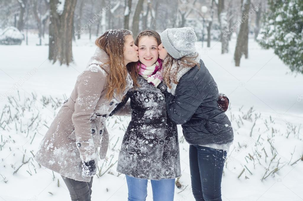 Two teenage girls kissing their girlfriend on snowy winter day