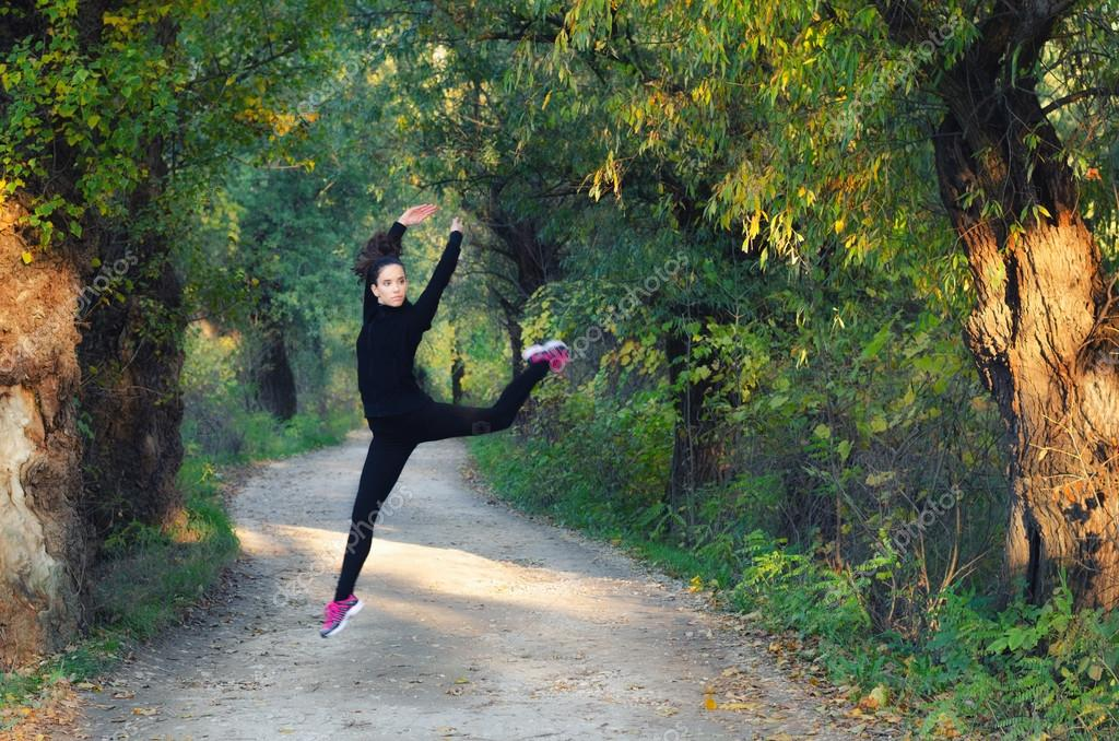 Beautiful ballerina girl jumping high in the air on road through autumn woods