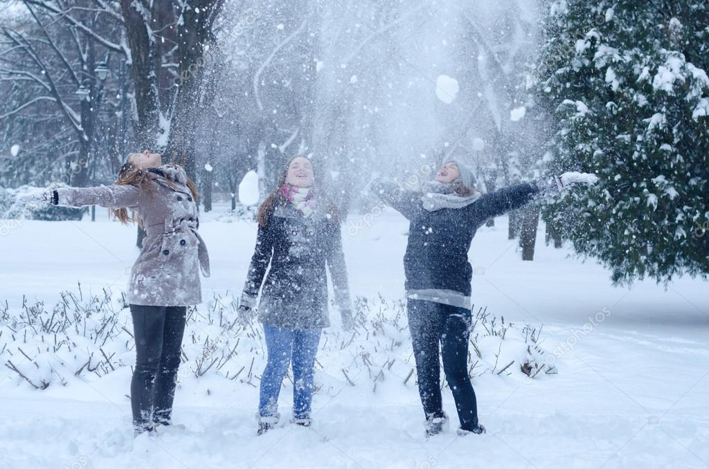 Three teenage girls throwing snow in the air on cold winter day