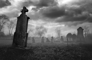 Old creepy graveyard on stormy winter day in black and white