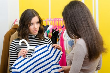 Saleswoman showing clothes to the young female customer