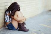 Smutná dívka siitng cihlová zeď