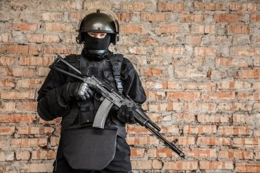 Special forces operator in black uniform and bulletproof stock vector