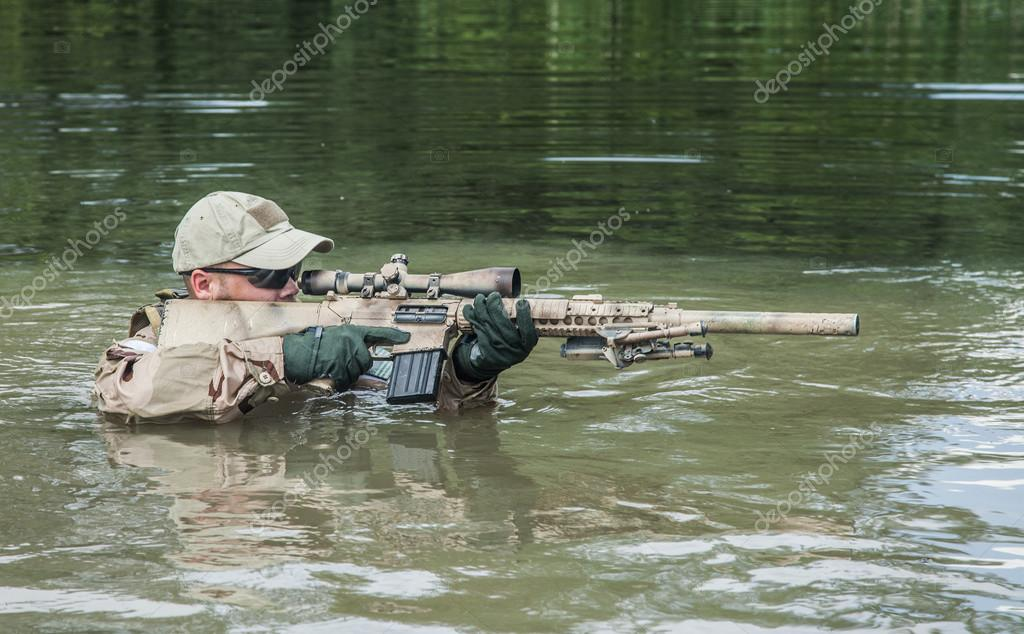 Member of Navy SEAL Team crossing the river with weapons stock vector
