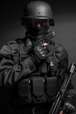 Spec ops police officer SWAT in black uniform with pistol studio stock vector