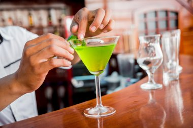 male hands attaching mint on Cocktail