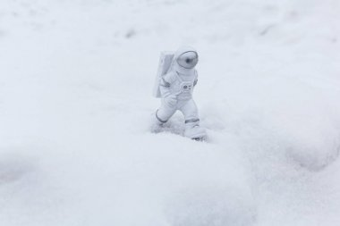 Statuette of an astronaut confidently explores alien planets surface. Cold planet covered with snow.