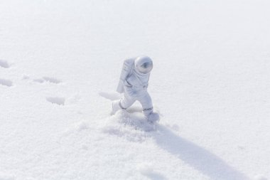 Statuette of an astronaut confidently explores alien planet's surface. Cold planet covered with snow. Copy space.