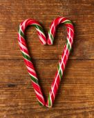 Candy canes on wooden board