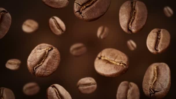 Pražená zrnková káva padá před tmavé pozadí.