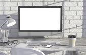 PC obrazovky u cihlové zdi