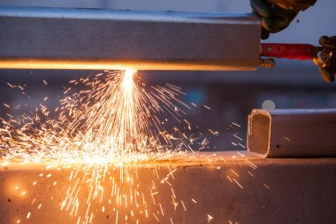 worker cutting steel pipe using metal torch and install roadside