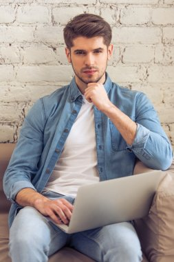 Attractive pensive young man is using a laptop and looking at camera while sitting on sofa at home stock vector