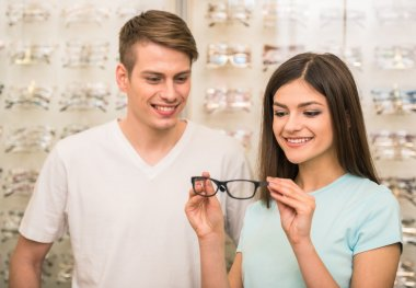 Young couple at optician in the store, they looking for glasses. stock vector