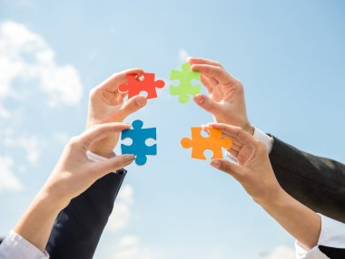 Closeup of business people wanting to put four pieces of puzzle together. Sky background. stock vector