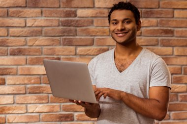 Young handsome Afro-American man using laptop, looking in camera and smiling while standing against brick wall stock vector